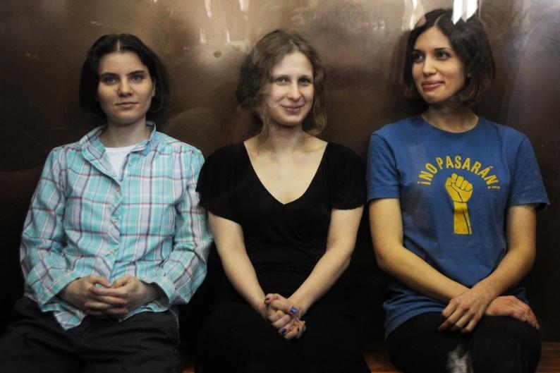 Maria Alyokhina, Yekaterina Samutsevich, and Nadezhda Tolokonnikova in a glass-walled cage / Photo by Getty Images