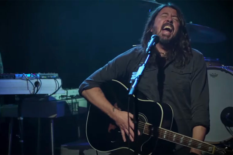 dave grohl of foo fighters singing and holding guitar