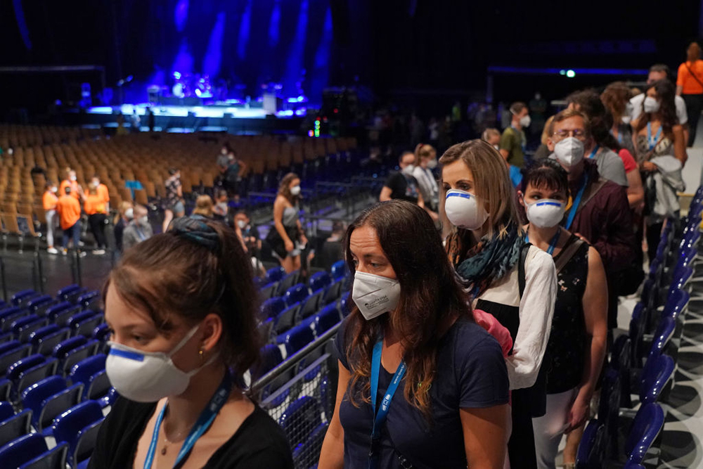 People wearing masks finding seats at an indoor venue