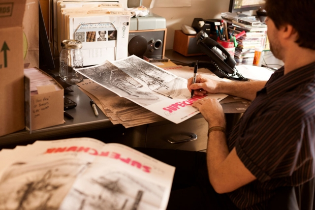 Wurster signs posters for the band's new record at the MERGE Records office. / Photo by Jeremy M. Lange